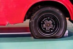 Uszkadzająca płaska opona stary czerwony samochód zdjęcia stock