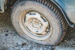 Uszkadzająca płaska opona stary samochód na drodze z selekcyjną ostrością Zdjęcia Stock