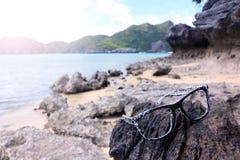 Uszkadzający okulary przeciwsłoneczni na skałach na plaży zdjęcia royalty free