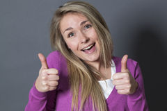 Utåtriktad 20-talkvinna med dubbla tummar upp Arkivbilder