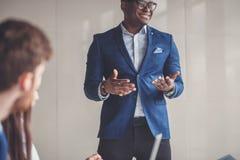Utövande affärsman för stilig gladlynt afrikansk amerikan på workspacekontoret Royaltyfri Bild