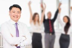 Utövande asiatiskt framstickande med hans lyckade affärslag på bakgrund Fotografering för Bildbyråer