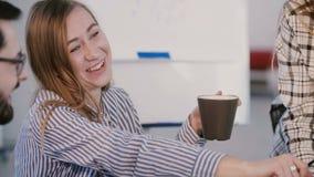 Utövande chef för ungt lyckligt kvinnligt kontor som ler och skrattar med kaffe på det informella lagmötet i modernt kontor arkivfilmer