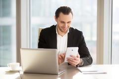 Utövande chef som använder mobilen app för att packa ihop Royaltyfria Bilder
