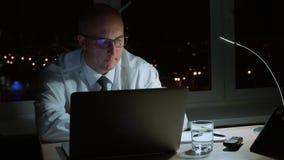 Utövande chef som i regeringsställning arbetar med bärbara datorn och dricksvatten på natten arkivfilmer