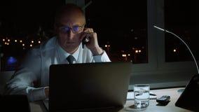 Utövande företags affärsmanworkig med bärbara datorn och mobil appell för danande i afton arkivfilmer
