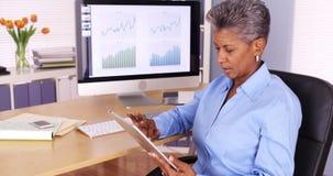 Utövande hög affärskvinna som arbetar på minnestavlan på skrivbordet Royaltyfri Fotografi