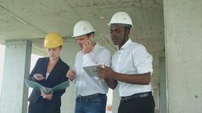 Utövande lag på konstruktionsplats som diskuterar projekt, genom att använda smartpone och den digitala minnestavlan stock video