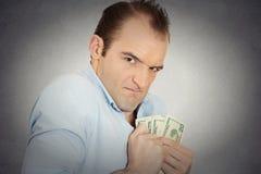 Utövande vdframstickande för girig bankir, hållande dollarsedlar Fotografering för Bildbyråer