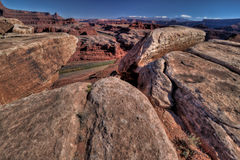 UT-Canyonlands National Pk-Wite Rim Rd. View of the Colorado River through the protection of the boulders near Walking Rocks off the White Rim Road in the Royalty Free Stock Images
