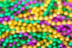 Ut ur fokusbakgrund av färgrika Mardi Gras pärlor arkivfoton
