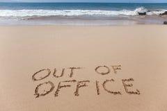 Ut ur kontoret som är skriftligt i sanden på en strand Fotografering för Bildbyråer