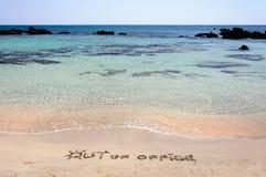 UT UR KONTORET som är skriftligt på sand på en härlig strand, vinkar blått i bakgrund Arkivbild