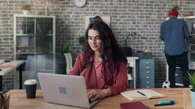Ut zoomar Time-schackningsperioden av den unga damen som använder bärbara datorn i det delade kontoret som fokuseras på jobb stock video