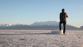 Utah Lake Frozen and Man Looking Tight. Man walking on frozen lake stops and looks stock video footage