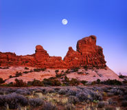 Utah Rock Forms And Moon. A Deep Blue Evening Sky And Full Moon Rising Over Red Sandstone Rock Forms At Arches National Park, Utah, USA Royalty Free Stock Images