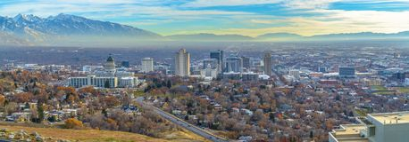 Utah State Capital Building and skyscrapers towering over the populous city. Snow capped mountain and cloudy blue sky can be seen in teh scenic background royalty free stock images