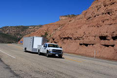 Utah: Truck towing enclosed trailer. Image of a truck on the highway towing an enclosed trailer against a red rock background royalty free stock images