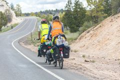 UTAH, USA - MAY 25, 2015: Bike trip in Utah USA. Two travelers riding bikes with many bags on mountain road. UTAH, USA - MAY 25, 2015: Bike trip in Utah USA. Two stock image