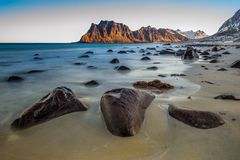 Utakleiv beach with rocks at sunrise. Utakleiv beach, Lofoten, Norway, a fantastic sandy and rocky beach at sunrise stock image