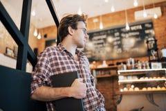 Utalentowany młody człowiek w przypadkowym koszulowym rysunku nakreśleniu w notatniku cieszy się wolnego czas w sklep z kawą Wykw zdjęcie royalty free