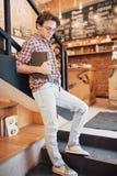 Utalentowany młody człowiek w przypadkowym koszulowym rysunku nakreśleniu w notatniku cieszy się wolnego czas w sklep z kawą Wykw fotografia stock