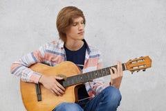 Utalentowany nastoletni chłopak jest ubranym koszula i cajgi trzyma gitarę akustyczną bawić się jego ulubione piosenki z modnym u fotografia stock