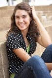 utanför den tonårs- sittande le deltagaren Royaltyfri Fotografi