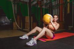 Utarbeta konditionkvinnan som att göra sitter ups övningar med medecinebollen Royaltyfri Foto