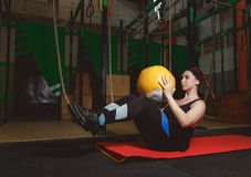 Utarbeta konditionkvinnan som att göra sitter ups övningar med medecinebollen Royaltyfria Bilder