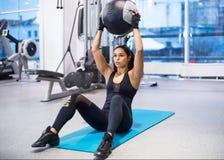 Utarbeta konditionkvinnan som att göra sitter ups buk- abs Royaltyfri Foto