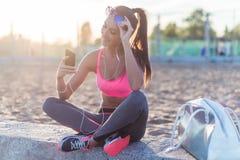 Utarbetar den bärande solglasögon för den härliga konditionidrottsman nenkvinnan som vilar lyssnande musik efter, att öva på somm arkivfoto