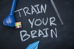 Utbilda din hjärninskrift på en svart tavla arkivfoto