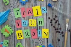 Utbilda din hjärninskrift på en träbakgrund arkivfoto