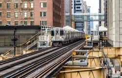 Utbilda på högstämda spår inom byggnader på den öglas-, exponeringsglas- och stålbron mellan byggnader - det Chicago centret - Ch Fotografering för Bildbyråer