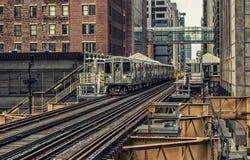 Utbilda på högstämda spår inom byggnader på den öglas-, exponeringsglas- och stålbron mellan byggnader - det Chicago centret - mö Arkivbilder