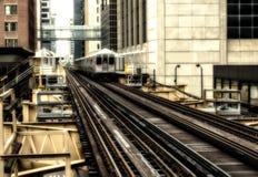 Utbilda på högstämda spår inom byggnader på den öglas-, exponeringsglas- och stålbron mellan byggnader - det Chicago centret - Se Arkivfoto