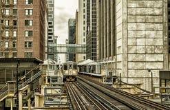 Utbilda på högstämda spår inom byggnader på den öglas-, exponeringsglas- och stålbron mellan byggnader - det Chicago centret - sv Fotografering för Bildbyråer