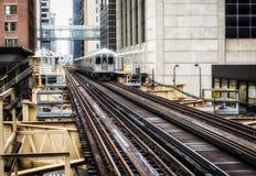 Utbilda på högstämda spår inom byggnader på den öglas-, exponeringsglas- och stålbron mellan mjuka byggnader - det Chicago centre Fotografering för Bildbyråer