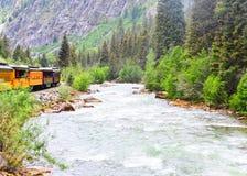 Utbilda spring längs en flod till och med bergen arkivbild