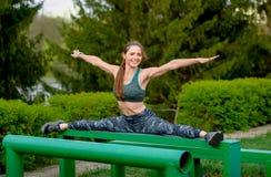Utbildande kropp till perfektion Den härliga flickan sträcker tvinnar på en sportjordning royaltyfri bild