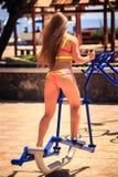 Utbildar den blonda flickan för baken i bikini på gradvist på sportjordning Arkivbild
