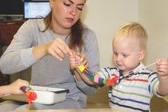 Utbildaren handlar med barnet i dagiset Kreativitet och utveckling av barnet royaltyfri bild