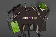 Utbildning av arkitektur - svart papper, text 'utbildning 'av träbokstäver som iscensätter hjälpmedel, förstoringsglas, glasögon royaltyfria foton