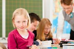 Utbildning - elever och lärare som lär på skolan Arkivfoto