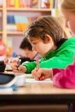 Utbildning - elever på skolan som gör läxa Royaltyfri Bild