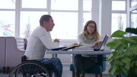 Utbildning för hög man för handikapp sjuk student i rullstol med handleder kvinnor under hem- undervisande använda för kurser lager videofilmer