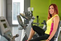 Utbildning för ung kvinna på en motionscykel Royaltyfri Foto