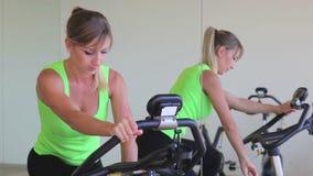 Utbildning för ung kvinna på motionscykelen lager videofilmer