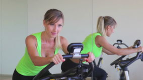 Utbildning för ung kvinna på motionscykelen stock video